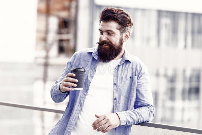 La mañana necesita cafeína. Hombre con barba beber cafeína caliente beber al aire libre Suspensión de hipster con bebida energéti foto de archivo libre de regalías
