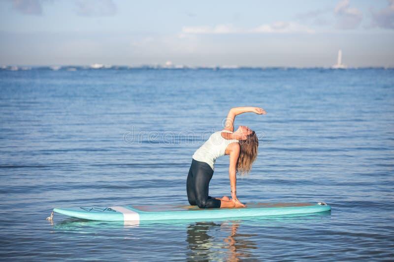 La mañana soleada resuelve a una mujer bastante joven en la parte posterior ben de la yoga del SORBO imágenes de archivo libres de regalías