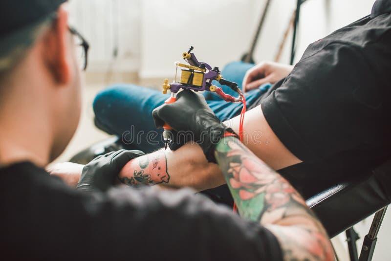 La macchina del tatuaggio fa attingere la mano maschio fotografia stock libera da diritti