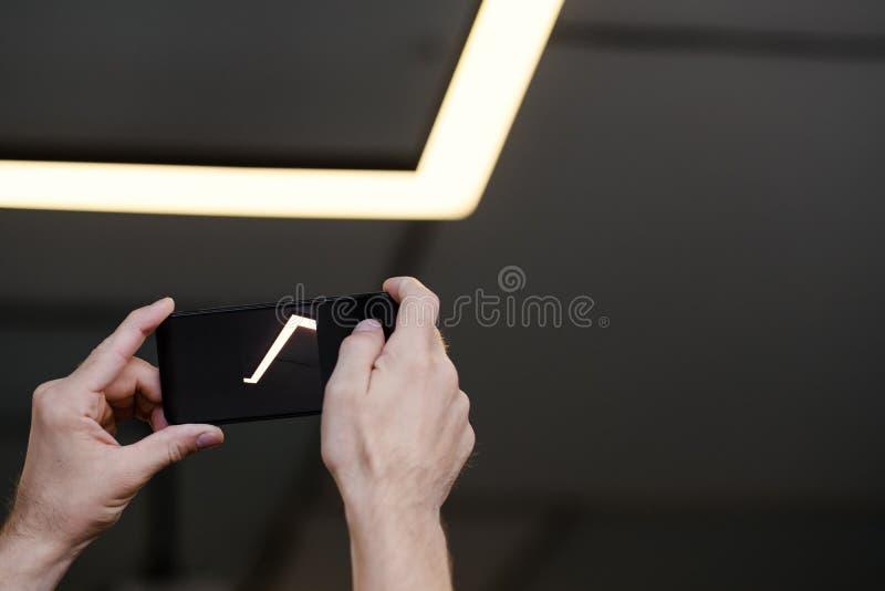 La macchina fotografica d'accensione interna moderna del telefono si è illuminata fotografia stock