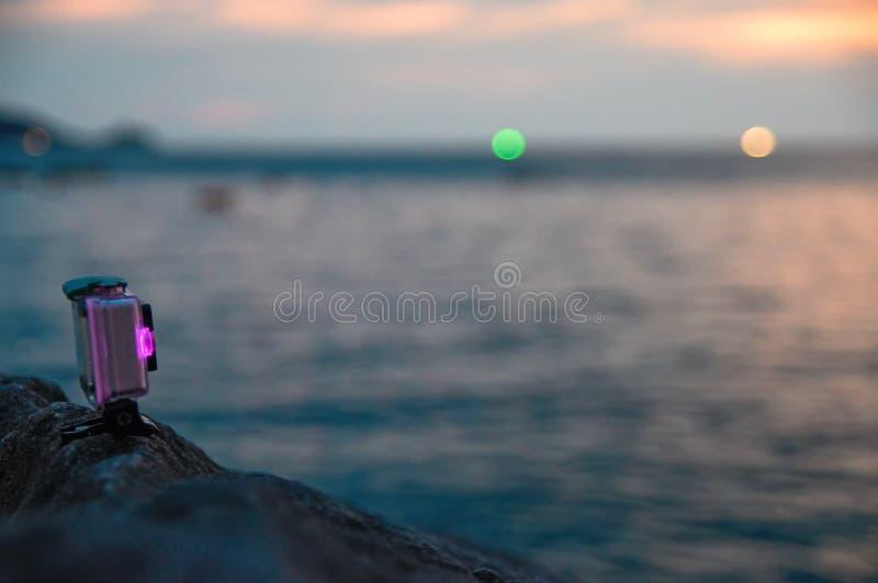 La macchina fotografica di azione con il diodo rosa luminoso sta su roccia sopra il mare di sera L'indicatore della batteria del  immagine stock