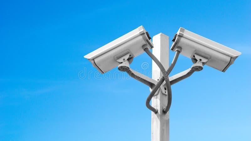 La macchina fotografica doppia del cctv di sorveglianza sul palo con cielo blu e copyspace, usa per la videosorveglianza ed il co immagini stock libere da diritti