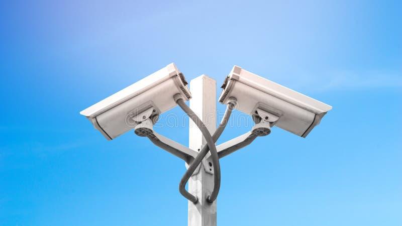 La macchina fotografica doppia del cctv di sorveglianza sul palo con cielo blu e svasarsi effetto della luce, usa per la videosor immagine stock libera da diritti