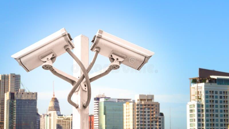 La macchina fotografica doppia del cctv di sorveglianza sul palo nella torre della città con effetto della luce del chiarore e co fotografie stock