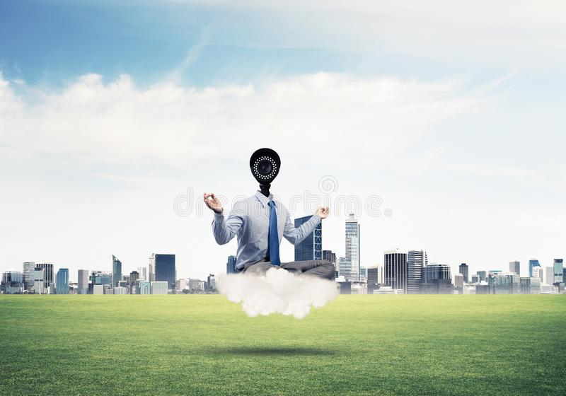La macchina fotografica ha diretto l'uomo che si siede nella posa del loto sulla nuvola contro moderno fotografia stock