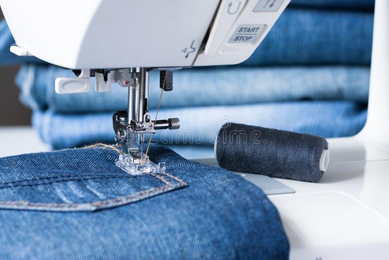 La macchina per cucire cuce il tessuto dei jeans immagine stock