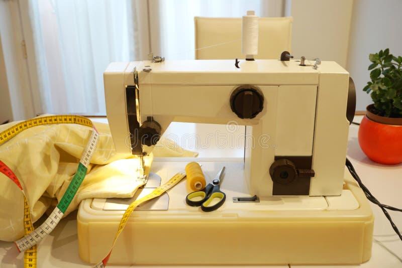 La macchina per cucire e gli accessori, il tessuto, la misura di nastro, infilano e lavorano all'uncinetto le forbici fotografia stock libera da diritti