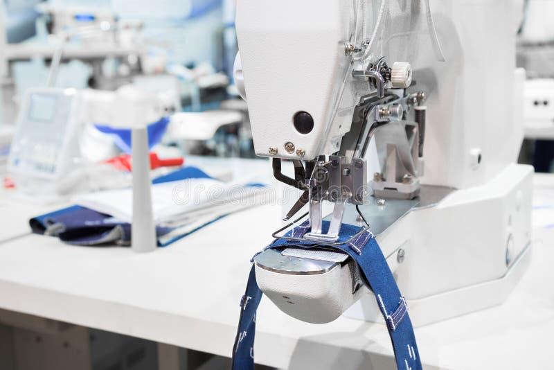 La macchina per cucire elabora una cucitura sul tessuto dei jeans fotografia stock