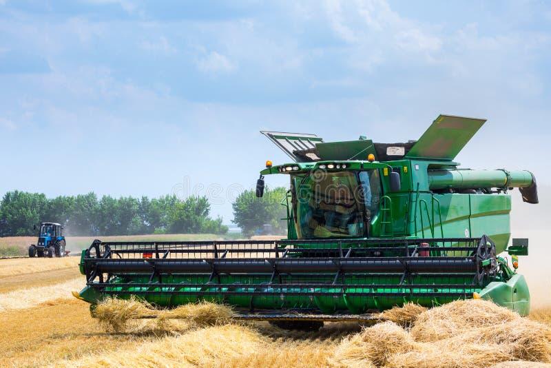 La macchina per effettuare i raccolti del grano - la mietitrebbiatrice nell'azione sul giacimento della segale al giorno di estat fotografia stock