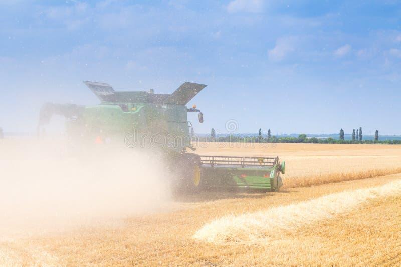 La macchina per effettuare i raccolti del grano - la mietitrebbiatrice nell'azione sul giacimento della segale al giorno di estat fotografia stock libera da diritti