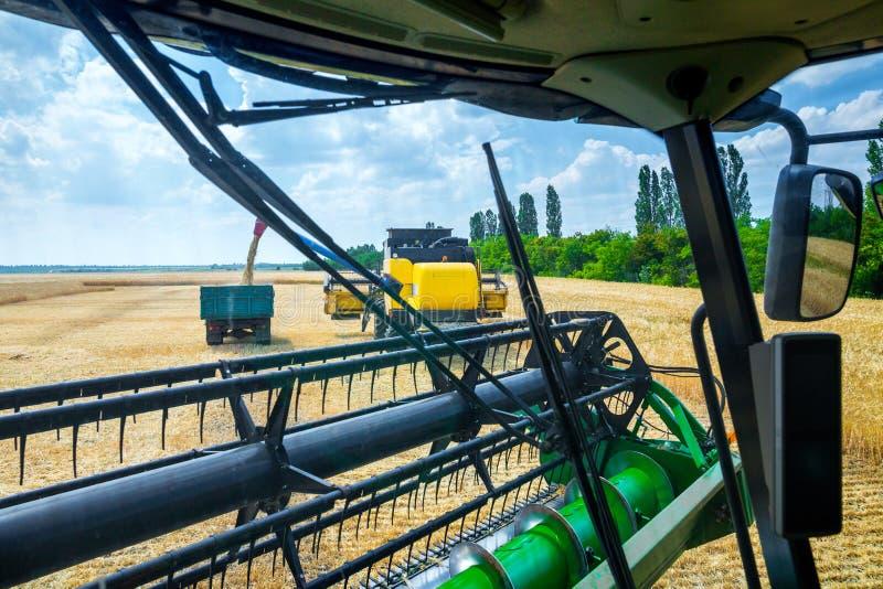 La macchina per effettuare i raccolti del grano - la mietitrebbiatrice nell'azione sul giacimento della segale al giorno di estat immagini stock libere da diritti
