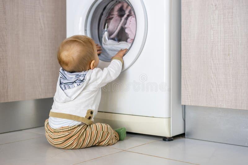 La machine à laver blanche garde occupé le petit bébé garçon photographie stock libre de droits