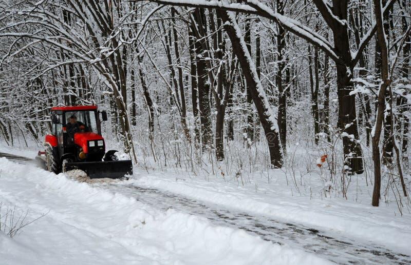 La machine de neige, tracteur rouge nettoie la neige de la neige à l'arrière-plan de la forêt image libre de droits