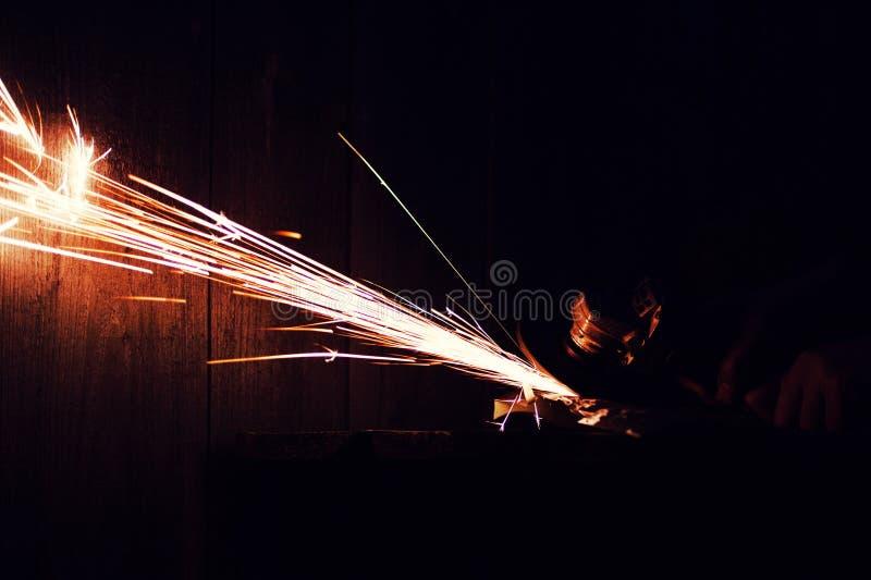 La macinazione del metallo sul tubo d'acciaio con il flash delle scintille si chiude su immagini stock libere da diritti