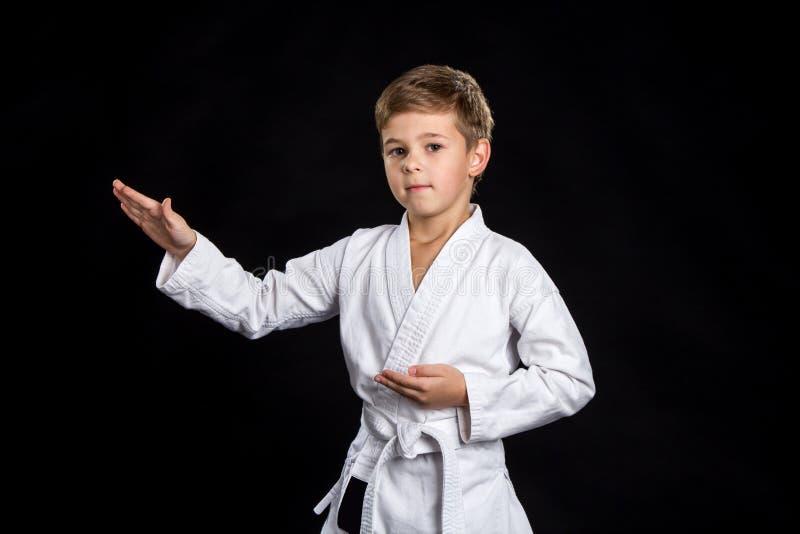 La macro con il combattente maschio nelle manifestazioni del kimono posa con le palme aperte Bambino serio in kimono nuovissimo s immagini stock libere da diritti