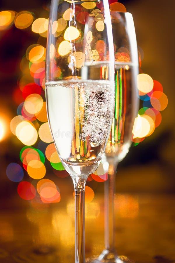 La macro di champagne ha versato dentro i vetri contro le luci di Natale immagini stock