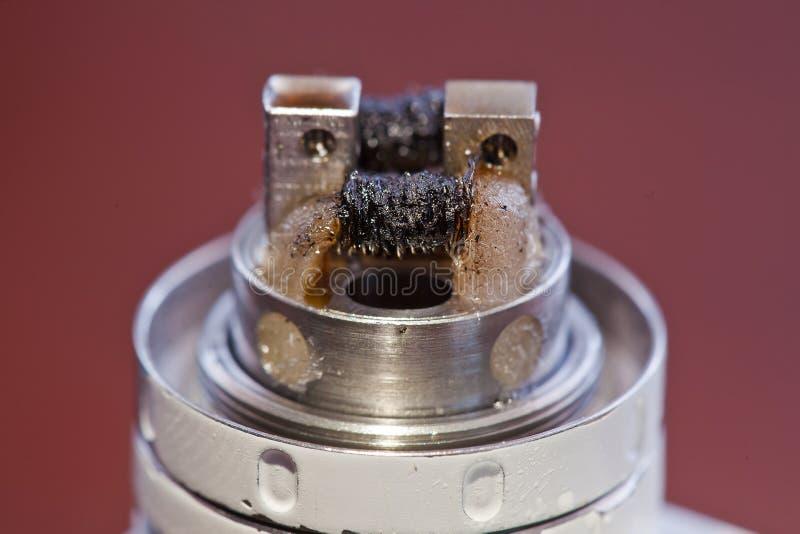La macro foto della bobina torta sporca ha montato nella sigaretta elettronica fotografia stock libera da diritti