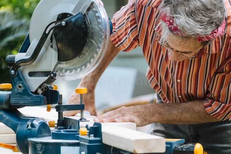 La madera del sawing del hombre con el desplazamiento del inglete compuesto vio foto de archivo libre de regalías