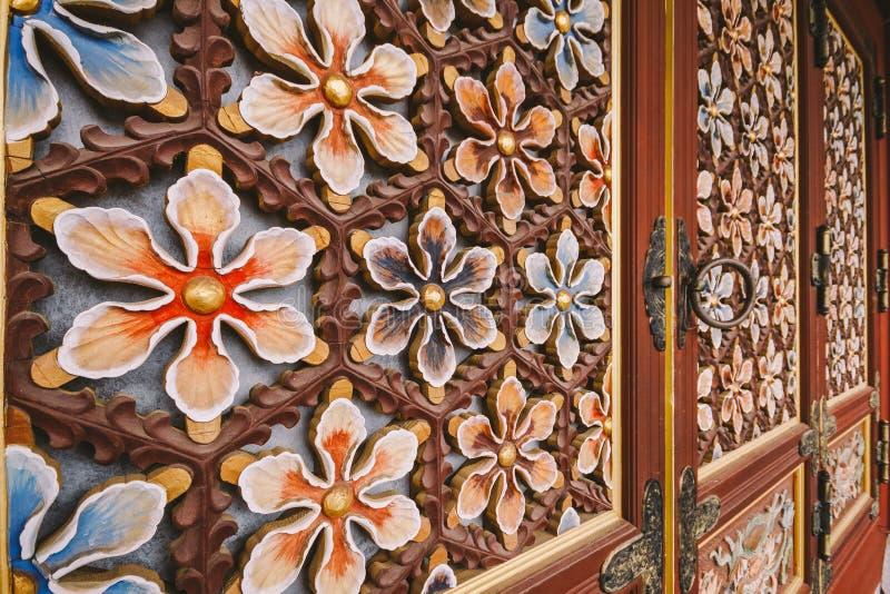 La madera florece la decoración de la puerta en el templo de Yakcheonsa Jeju, Corea del Sur imagenes de archivo