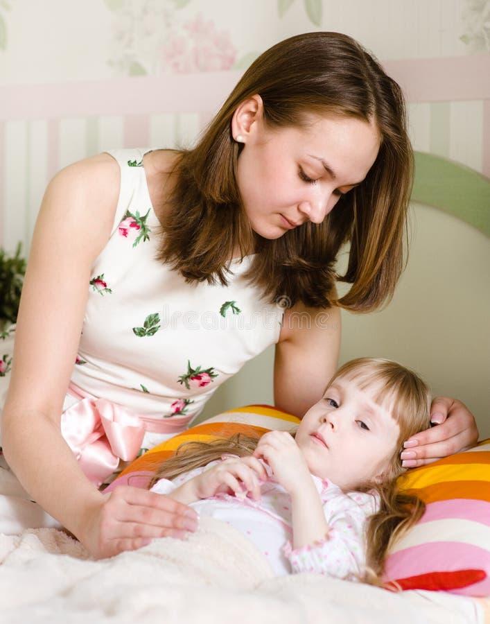 La madre abraza al niño enfermo imagen de archivo