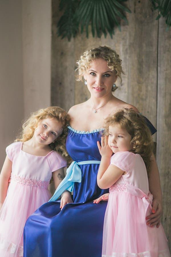 La madre abraza a hijas gemelas hermosas foto de archivo