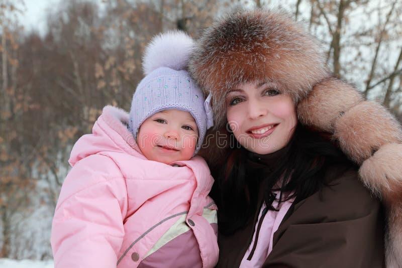La madre abraza a la hija en el invierno imagenes de archivo