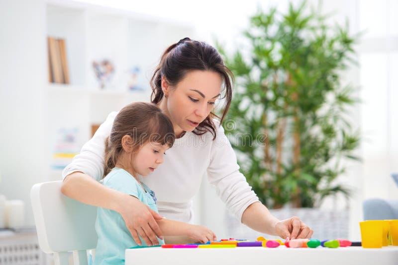La madre aiuta una piccola figlia a scolpire le figurine da plasticine Creatività del ` s dei bambini Famiglia felice immagini stock