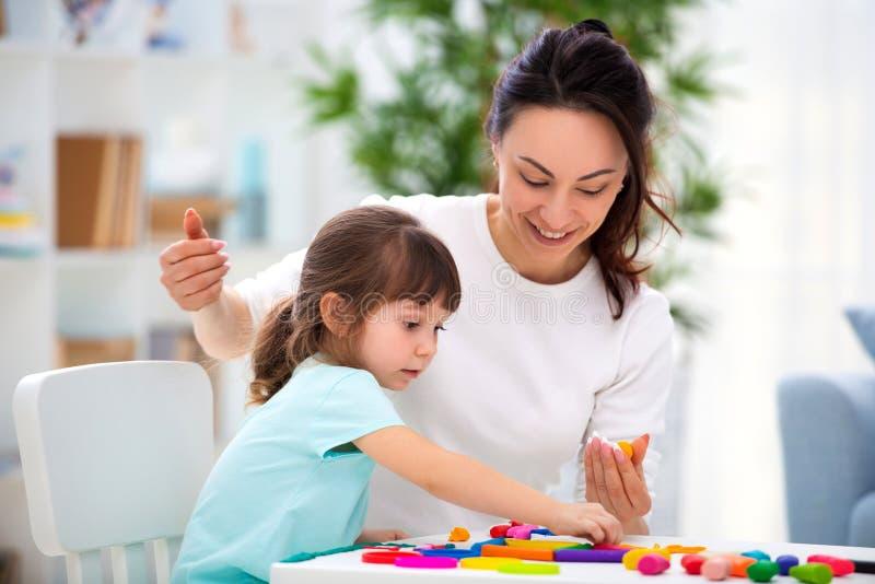 La madre aiuta una piccola figlia a scolpire le figurine da plasticine Creatività del ` s dei bambini Famiglia felice fotografie stock libere da diritti