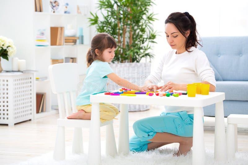 La madre aiuta una piccola figlia a scolpire le figurine da plasticine Creatività del ` s dei bambini Famiglia felice fotografia stock
