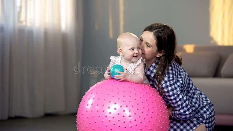 La madre alegre que juega con el niño, haciendo aptitud del bebé ejercita en bola grande foto de archivo
