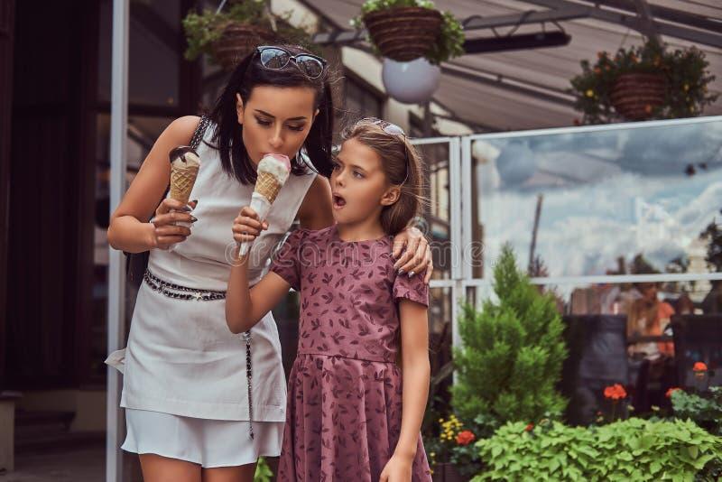 La madre alla moda e la figlia sveglia godono del gelato un giorno di estate caldo fotografia stock libera da diritti