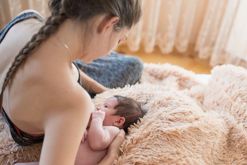 La madre amamanta madre hermosa feliz con el bebé en cama en casa alimente al bebé antes de cama fotos de archivo