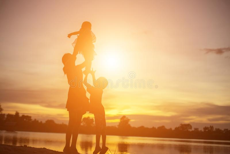 La madre anim? a su hijo al aire libre en la puesta del sol, concepto de la silueta fotografía de archivo libre de regalías