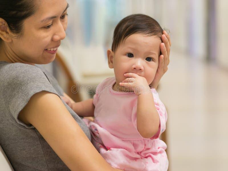 La madre asiática lleva al bebé interior imagenes de archivo