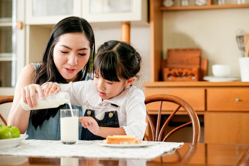 La madre asiática lleva para cuidar a su hija para verter la leche un vidrio en la tabla en cocina de la casa durante comida del  fotos de archivo