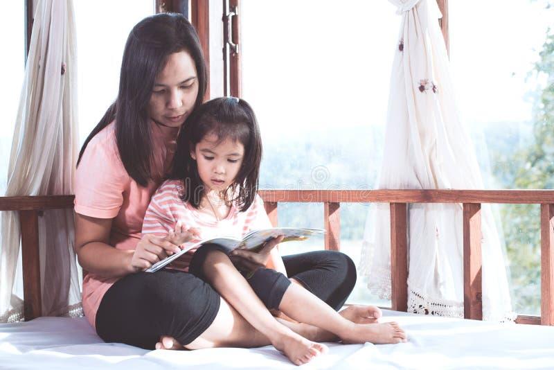 La madre asiatica e la figlia della famiglia felice hanno letto insieme un libro immagini stock libere da diritti