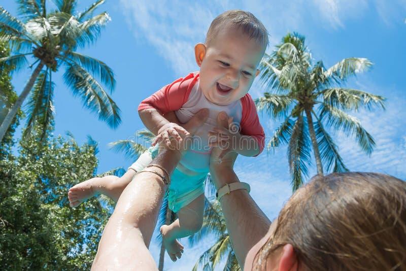 La madre aumentó para arriba alto infantil del niño sobre la cabeza en la piscina El pequeño bebé es muy feliz y gritos para la a fotografía de archivo libre de regalías