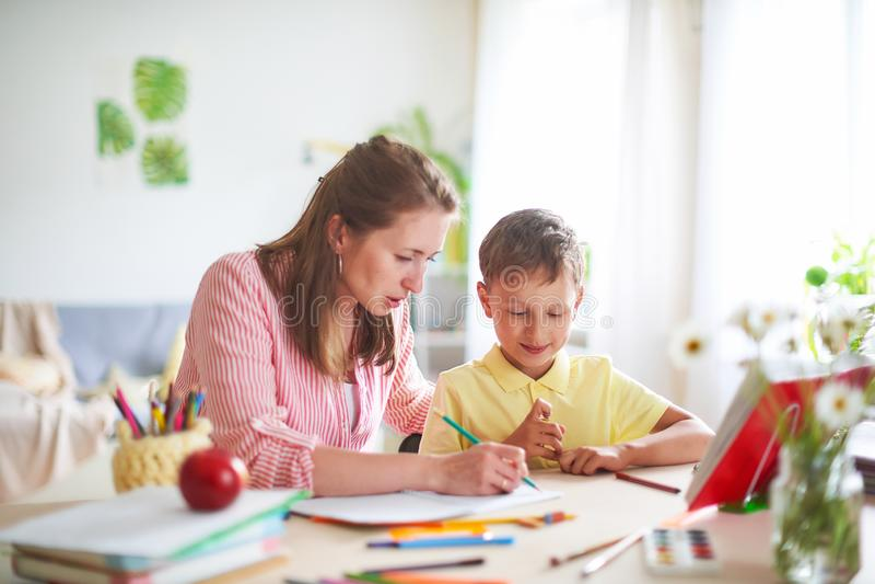 La madre ayuda al hijo a hacer lecciones el enseñar casero, lecciones caseras el profesor particular se involucra con el niño, en fotografía de archivo