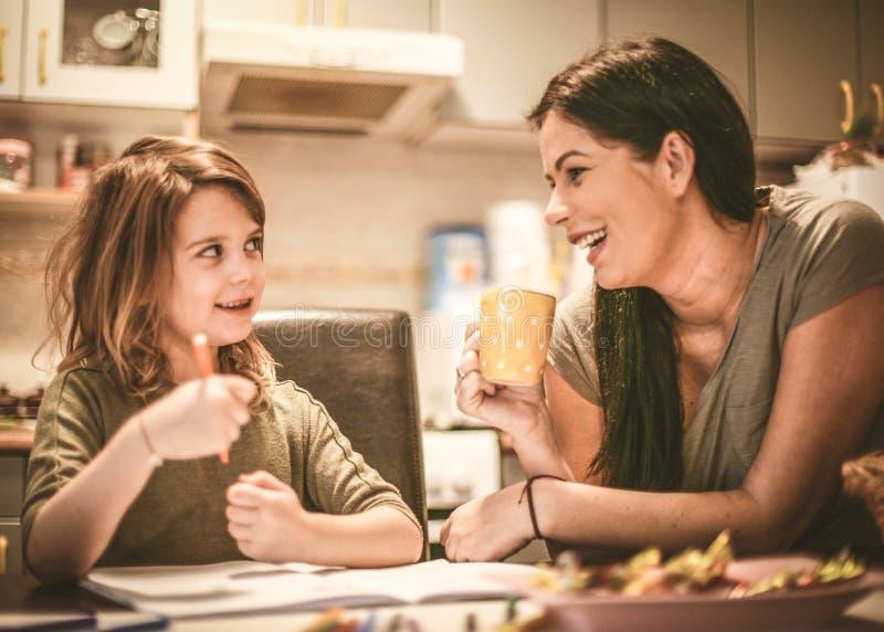 La madre ayuda a la hija a dibujar Cierre para arriba imagenes de archivo