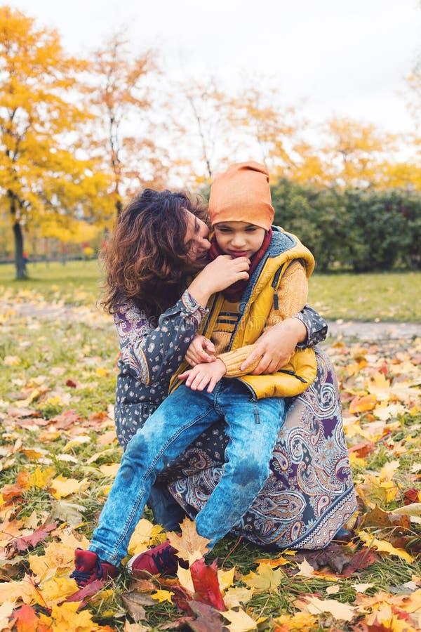 La madre ayuda a su niño en parque al aire libre foto de archivo