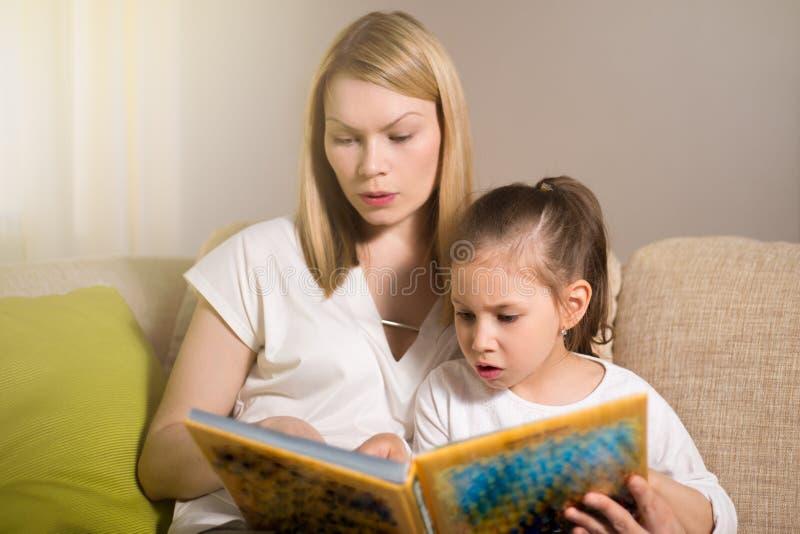 La madre bastante hermosa y su hija joven están leyendo un libro fotografía de archivo