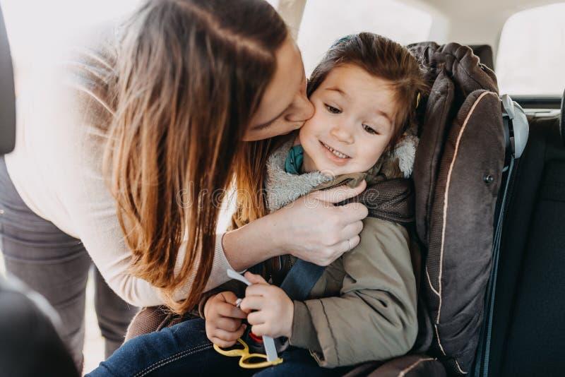 La madre besa a su hija del niño abrochada en su asiento de carro del bebé fotografía de archivo libre de regalías
