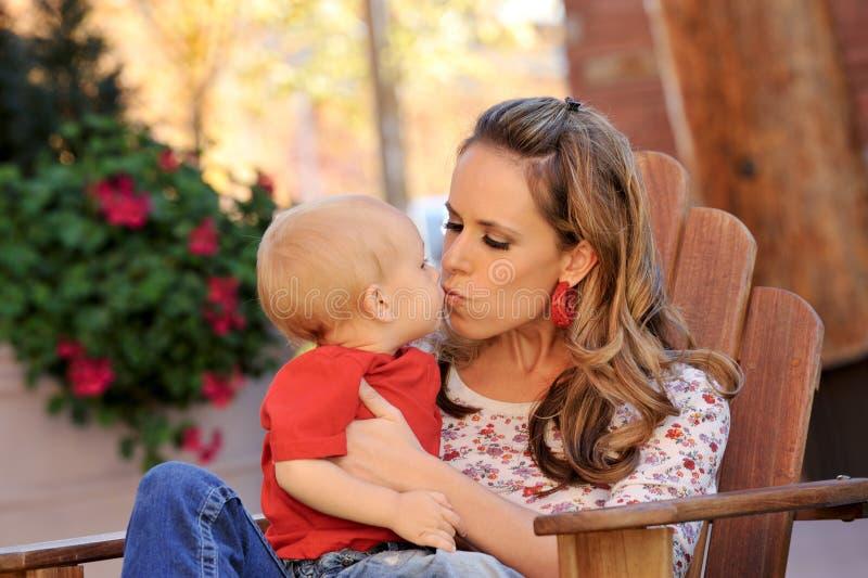 La madre besa a su niño imagen de archivo