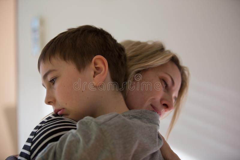 La madre bionda ed il ragazzo castana si abbracciano caldo Luce dell'interno e naturale fotografia stock libera da diritti
