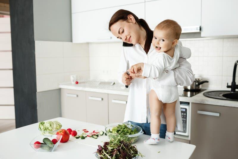 La madre cabelluda oscura hermosa cocina la ensalada para el desayuno y hablar en el teléfono mientras que pequeño hijo lindo que foto de archivo libre de regalías