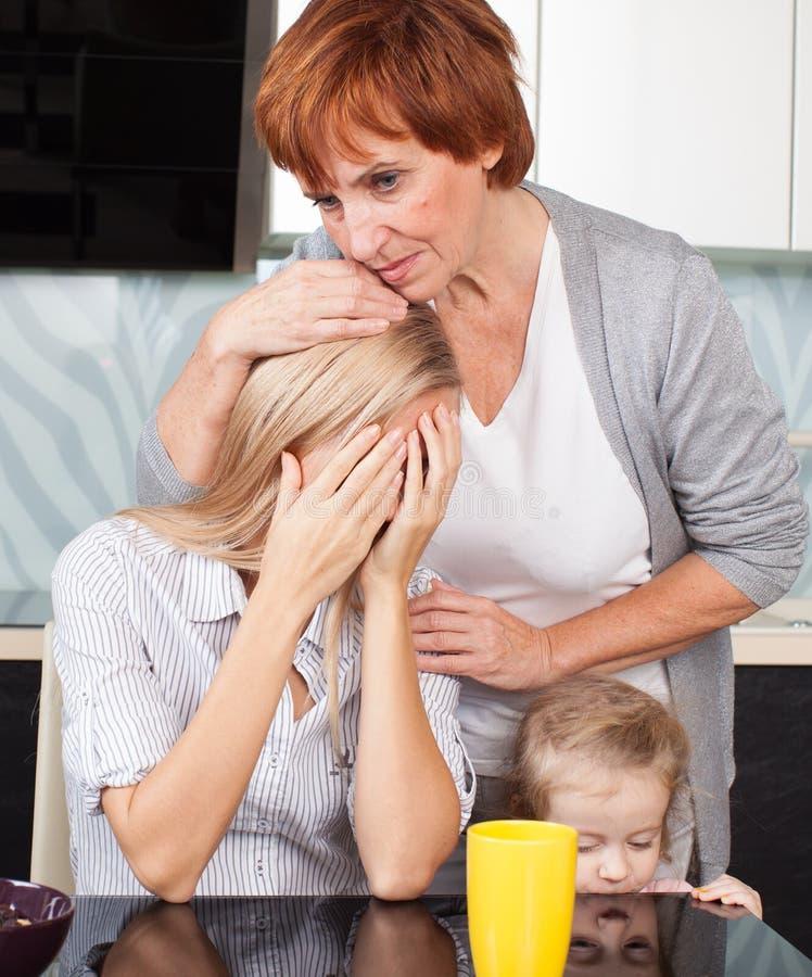 La madre calma a la hija triste imagenes de archivo