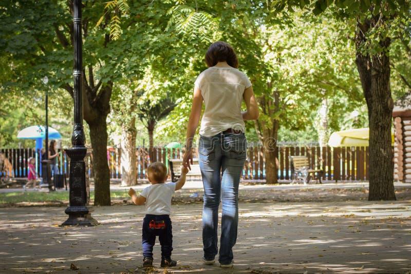 La madre camina con su niño que lleva a cabo su mano en el parque del otoño Concepto responsable de la paternidad foto de archivo