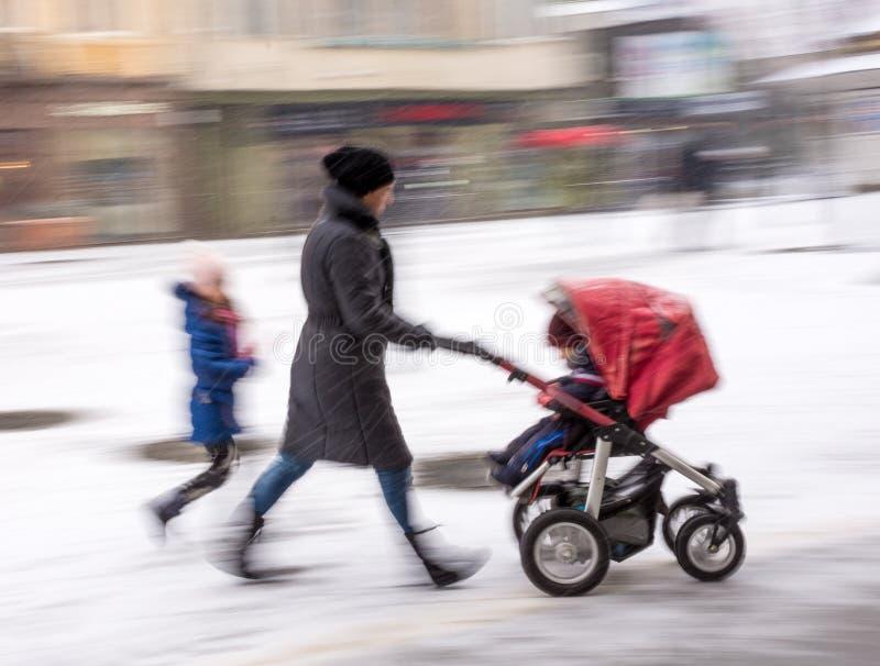 La madre cammina con il bambino nel passeggiatore nel giorno nevoso del winetr fotografia stock libera da diritti