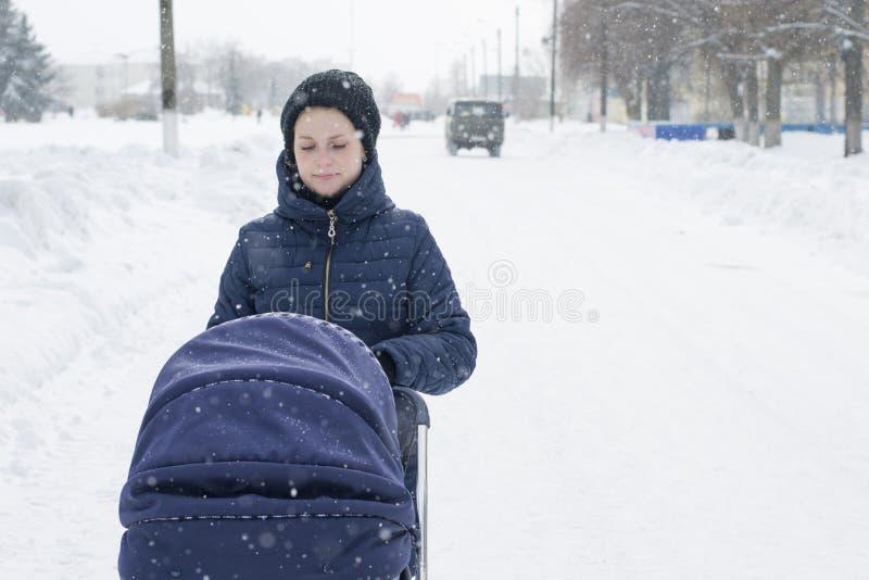La madre cammina con un passeggiatore un giorno di inverno nevoso fotografia stock libera da diritti