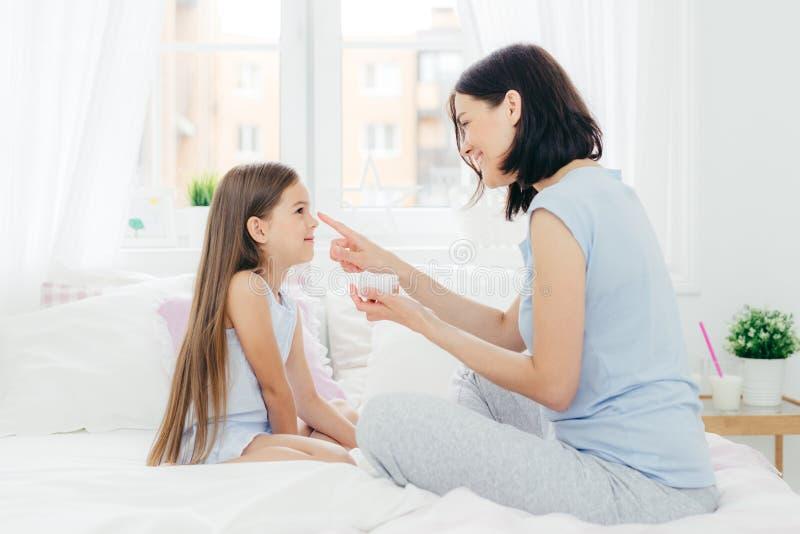 La madre cariñosa aplica la crema en la nariz de la hija, sienta el toget foto de archivo